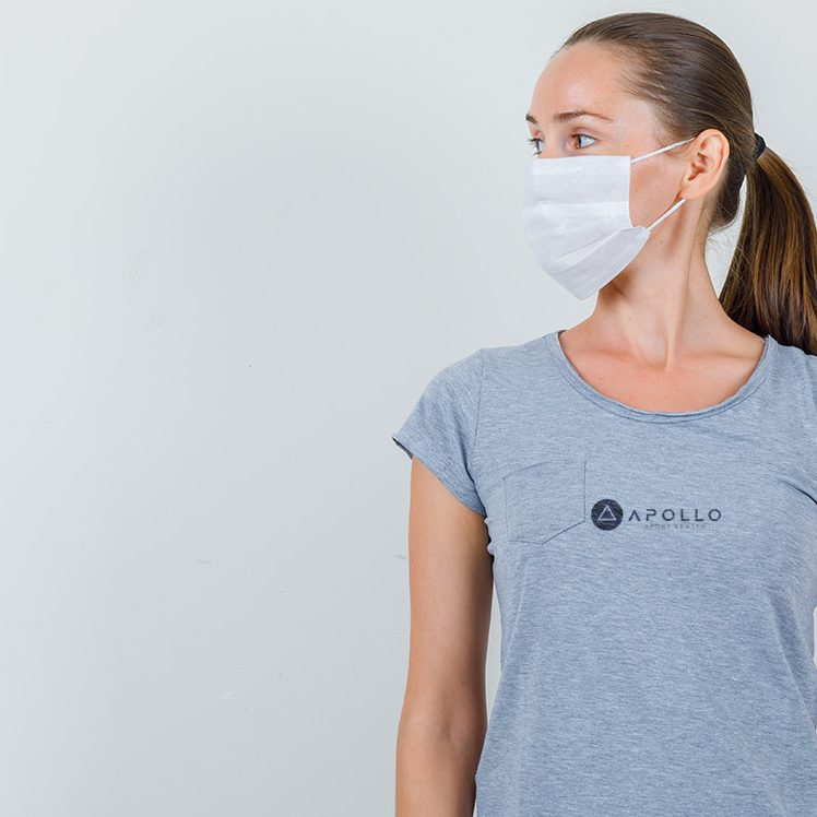 Young woman looking aside in grey t-shirt, mask , front view.